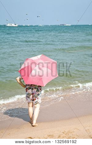 Elderly woman dressed in shorts with a pink umbrella standing on a beach sand sunbathing watching at the sea horizon