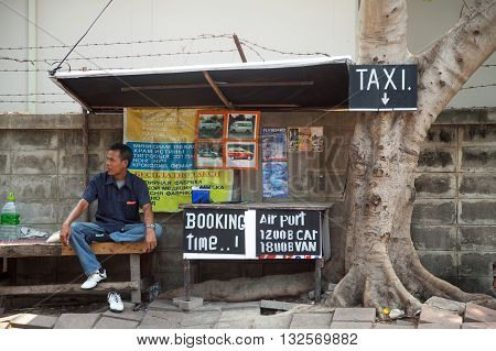 PATTAYA / THAILAND - MARCH 22, 2016: Thai taxi driver waiting for customers next to advertisement. Street taxi service