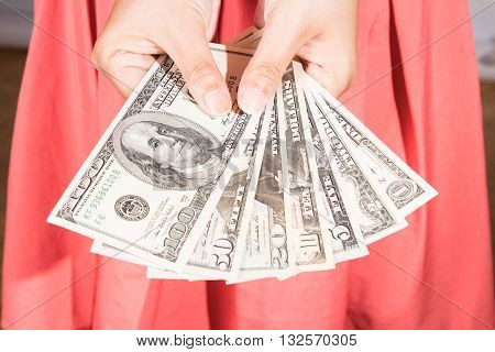 a woman hold dollar banknote in hand