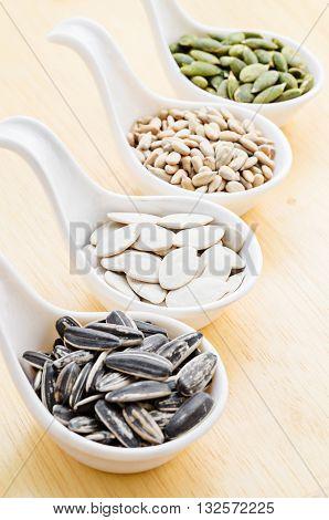 sunflower seeds and pumpkin seeds on wood background