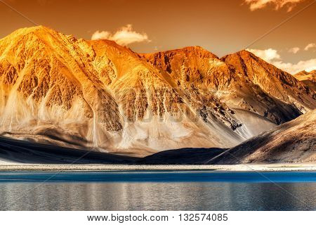 Beautiful Mountains and Pangong tso (Lake) in sun set. A huge lake in Ladakh extends from India to Tibet. Leh Ladakh Jammu and Kashmir India. Himalayan mountains in background. Colourful image.