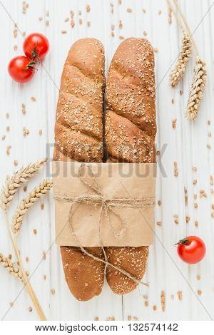 Two loafs of French baguette bread tied with paper and string on white wooden background, with wheat grain and cherry tomatoes