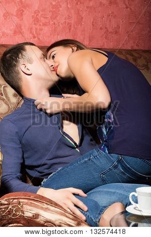problems in family relationships, a young couple sitting on the couch. man hurt, woman sits astride a man and kisses him.