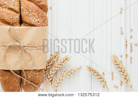 Two loafs of French baguette bread tied with paper and string on white wooden background, with wheat grain, copy space