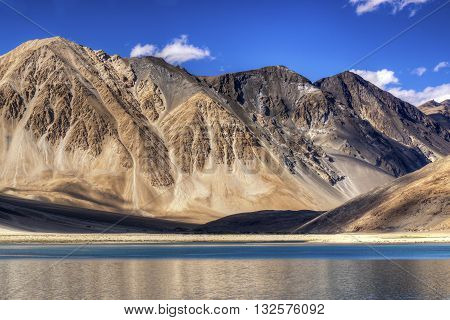 Beautiful Mountains and Pangong tso (Lake). It is a huge lake in Ladakh extends from India to Tibet. Leh Ladakh Jammu and Kashmir India. Himalayan mountains in background.
