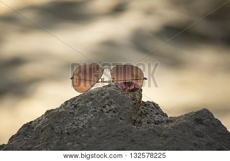 Red sunglasses on the rock in the beach, focus sunglasses