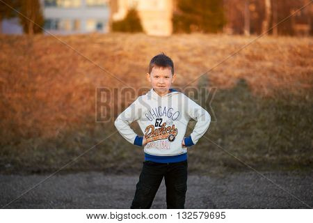 boy in pants, sneakers plays, enjoys running, kicking the ball, smiling