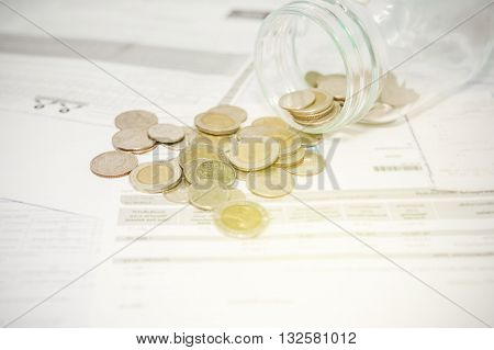 Close up of glass bottle stacking silver coins on paper bill, Vintage style
