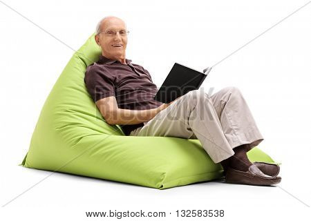 Relaxed senior man reading a book seated on a green beanbag isolated on white background