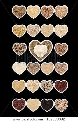 Grain food collection in heart shaped bowls over a black background.