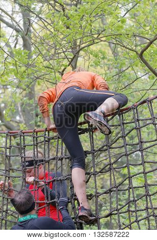 STOCKHOLM SWEDEN - MAY 14 2016: Woman climbing up a net in the obstacle race Tough Viking Event in Sweden May 14 2016