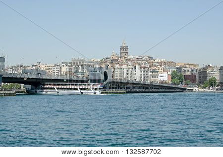 ISTANBUL TURKEY - JUNE 5 2016: View from the Old Town looking north across the Golden Horn along the Galata Bridge towards Karakoy district and the historic Galata Tower on a sunny afternoon in June.