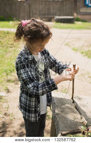 eight-year-old girl in a plaid shirt plays one on the street with a rope and a wooden stick in the village during summer