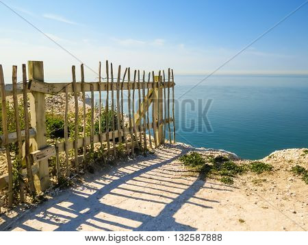 Old fence on the edge of the collapsing white chalk cliffs. East Sussex, England