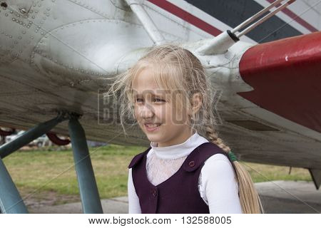 Girl and old airplane on airfield in summer day