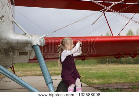 Girl And An Old Airplane On The Airfield