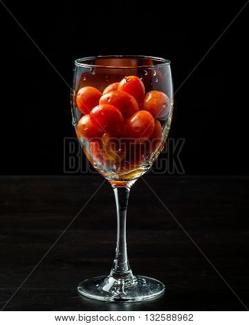 Fresh grape tomatoes in a glass. Tomatoes. Cherry tomatoes. Cocktail tomatoes. Black background.