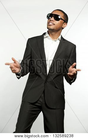A young vogue style black male wearing sunglasses, white button down shirt with a custom suit jacket in a studio setting on a white background.