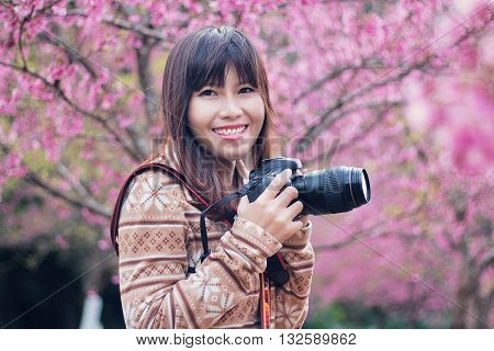 Women photographer smilling and take a picture in flowers gardening and blurred background