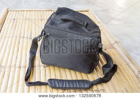 Black camera bag on bamboo floor. select focus front black camera bag.
