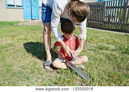Father Teaching Boy In Machete Sharpening