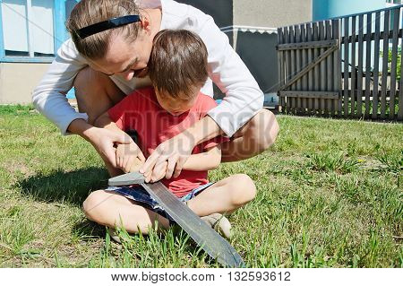 Dad Teaching Boy In Machete Sharpening