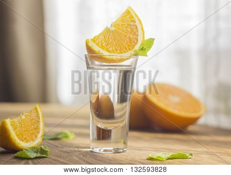 Tequila shot with orange slice and mint