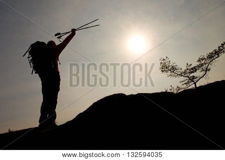 Silhouette Of Happy Tourist With Poles In Hand Above Head. Sunny Daybreak In Mountains. Hiker With S