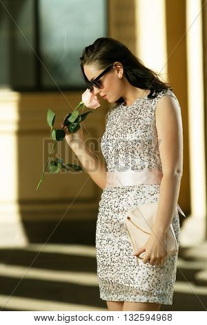 Beautiful girl with a rose in hand