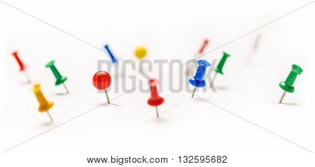 Colorful paper pins attached to white paper