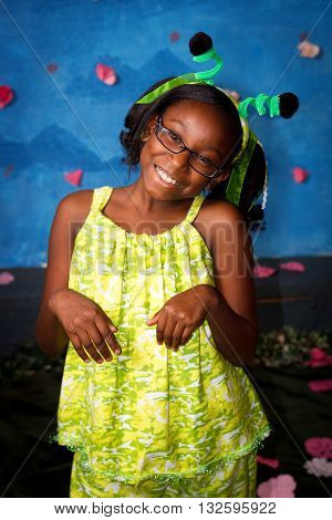 A cute tween african american girl poses for a picture while dressed in a praying mantis costume.