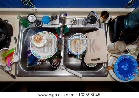 A messy sink full of dirty dishes. A house hold with kids. Real life image.