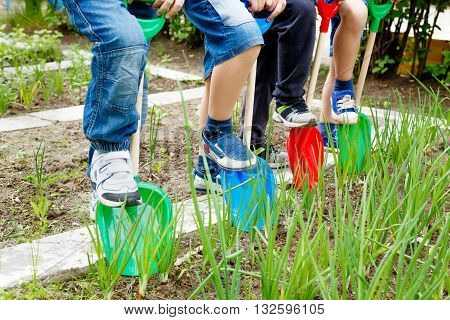 A group of children play with plastic shovels in the garden at summer day