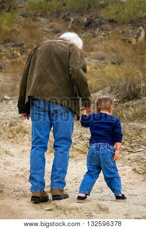A very young boy hiking with his grandfather. The two are heading up a slight hill in the desert and look to be walking cautiously. Grandpa has white hair.