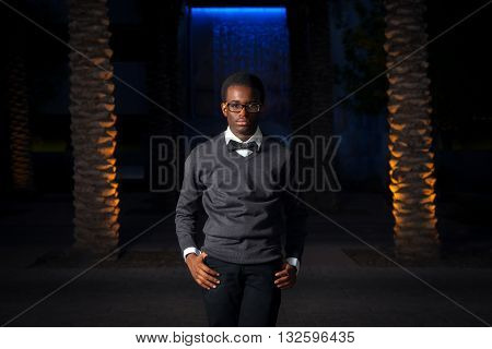 An intense african american teenage boy poses for a serious portrait in front of a blue waterfall at night.