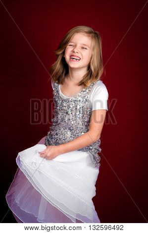Portrait of a laughing blond haired girl swishing her dress. She is missing two teeth and looks extremely happy.