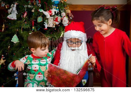 A young girl with a Santa hat and beard reads to a little girl and boy in front of a decorated Christmas tree.