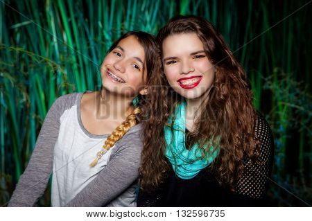 A portrait of two teenage sisters. The younger leans on her older sibling for support in an affectionate manner.