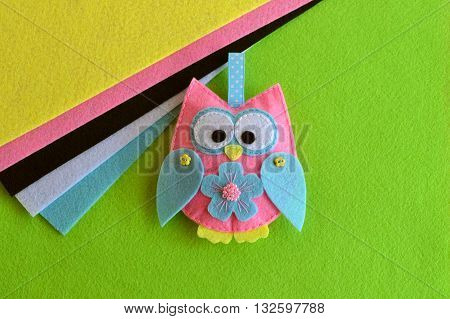 Colourful patchwork felt owl. Owl holiday decor. Hanging owl decoration. Nursery decor. Fabric bird made by hand. Pink, yellow, blue, white, black pieces of felt. Green background