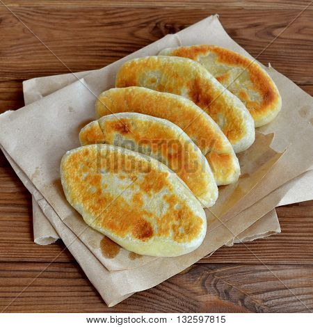 Tortilla dough stuffed with cheese on a paper and wooden background. Fried pies closeup. Easy delicious food recipe. Tasty snack idea. Homemade yummy fried pies with filling