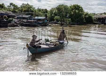 Houses and floating shops on the Siem Reap river. Siem Reap has a floating village with houses and shops like this. Tourist boats and merchants selling items on boats are seen.