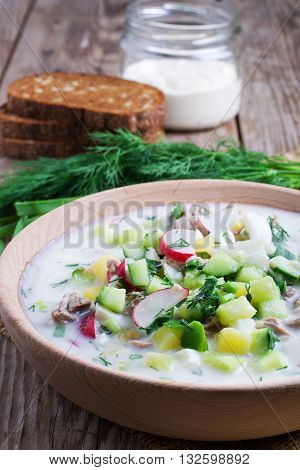 Okroshka on kefir with rye bread on a wooden table