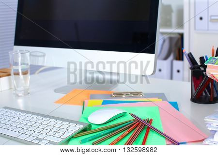 Designer working place with computer and paperwork.