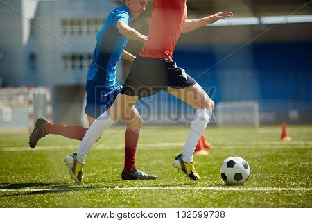 Two footballers running down field after ball