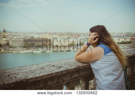 Woman Leans On The Railing And Watching The Horizon While Budapest Cityscape In Background