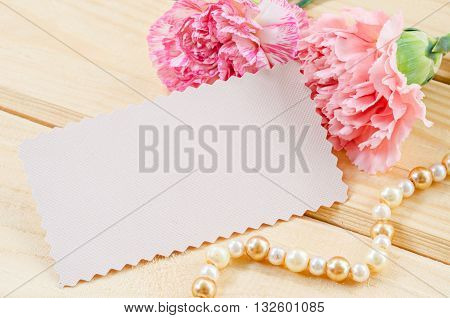 Blank white greeting card with pink Carnation flower on wooden background.