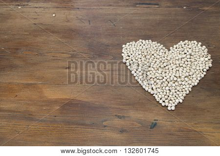 a heart drawn with vegetables on wooden background Legumes are excellent foods and recommended to replace meat and fish