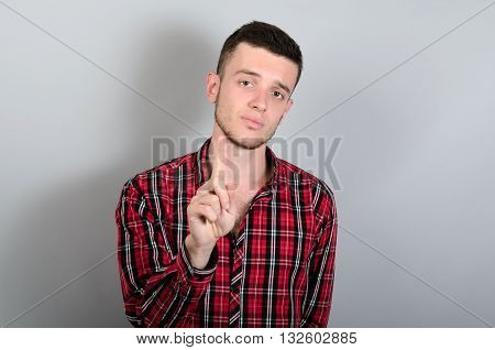 Man Pointing Up With His Index Finger Looking At Camera