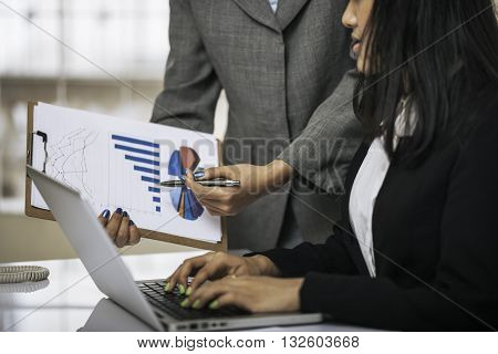 woman's hands holding sheet of charts and pointing