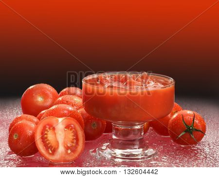 FRESH , RAW TOMATO SAUCE IN A GLASS , SURROUNDED WITH FRESH CHERRY TOMATOES , ON GRADIENT BACKGROUND